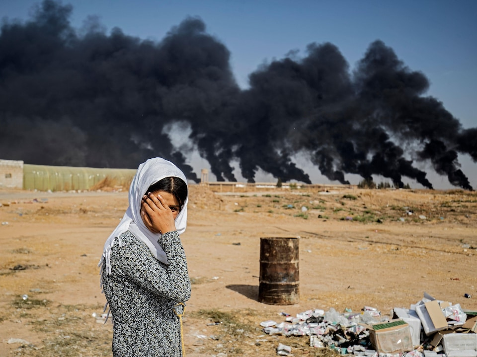Une jeune femme se couvre le visage. En arrière-plan, d'immenses colonnes de fumées noires.