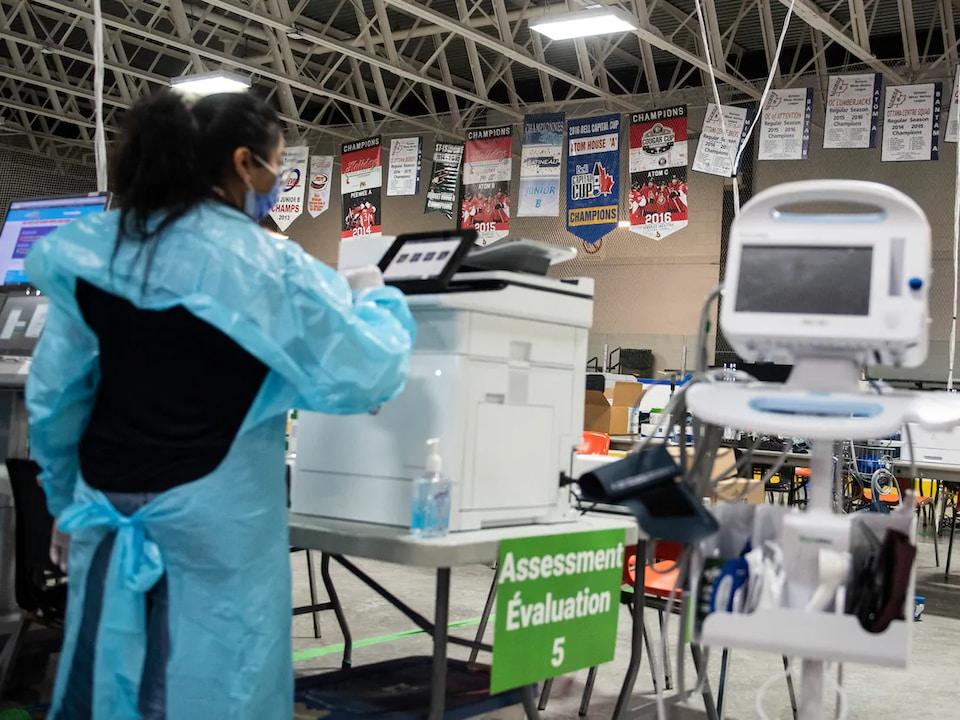 Une travailleuse de la santé analyse un test de dépistage de la COVID-19.