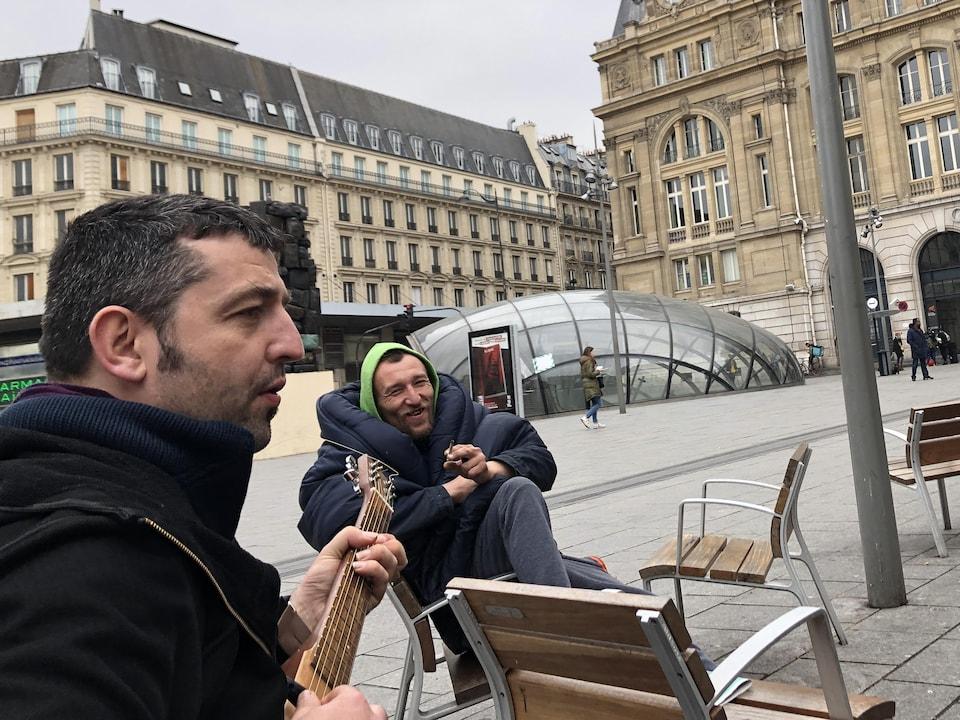 Fabien grille une cigarette en écoutant un homme qui joue de la guitare.