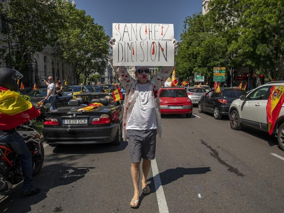 Un homme masqué marche dans une rue de Madrid en brandissant une pancarte sur laquelle il est écrit en espagnol: «Sanchez démissionne».