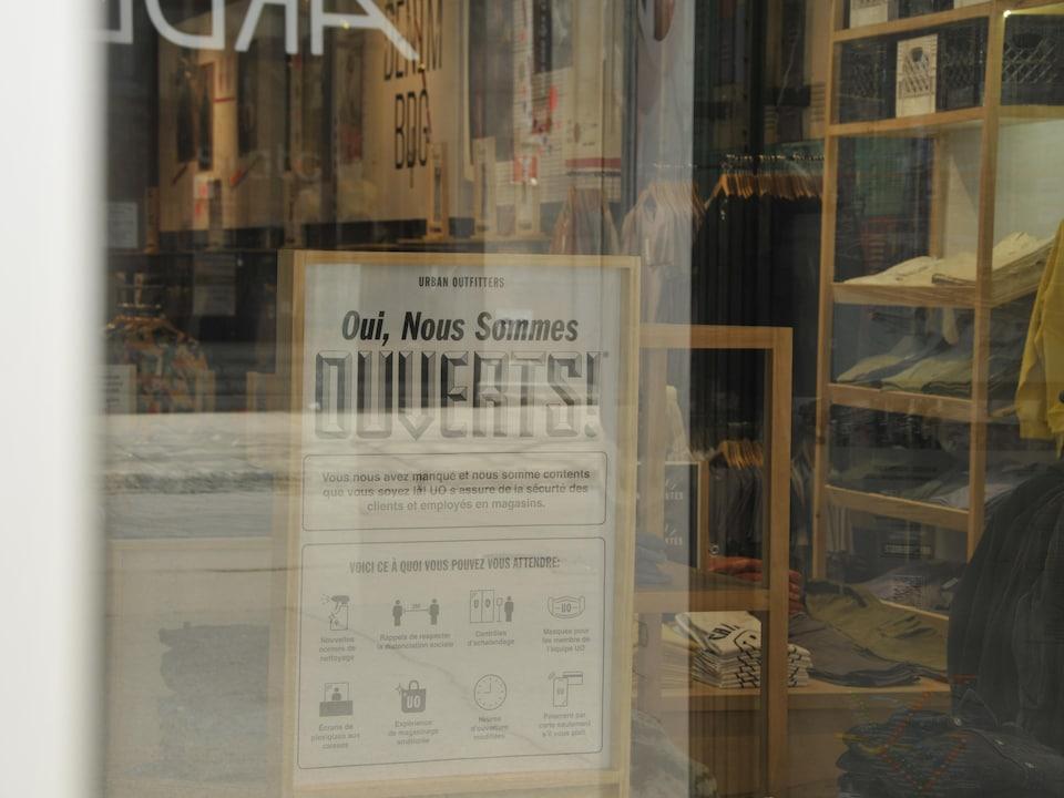 Une affiche dans un magasin de Montréal annonce sa réouverture et les règles d'hygiène à respecter.