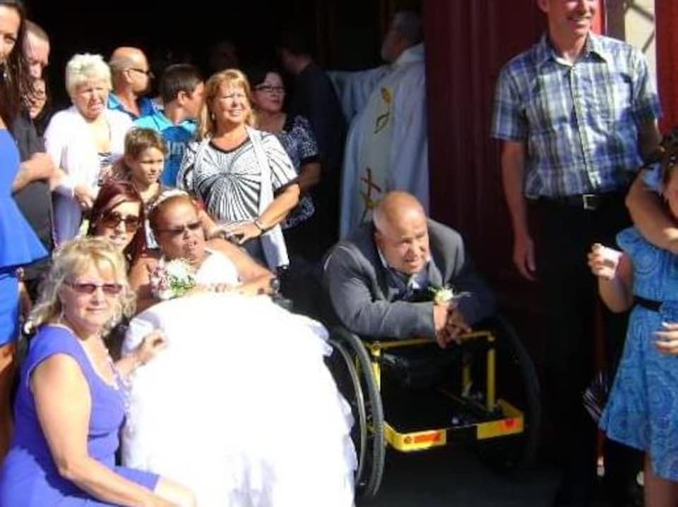 Gina Lepage et René Desmarchais, tous les deux en fauteuil roulant, à leur mariage sur le parvis de l'église avec des membres de leurs familles.