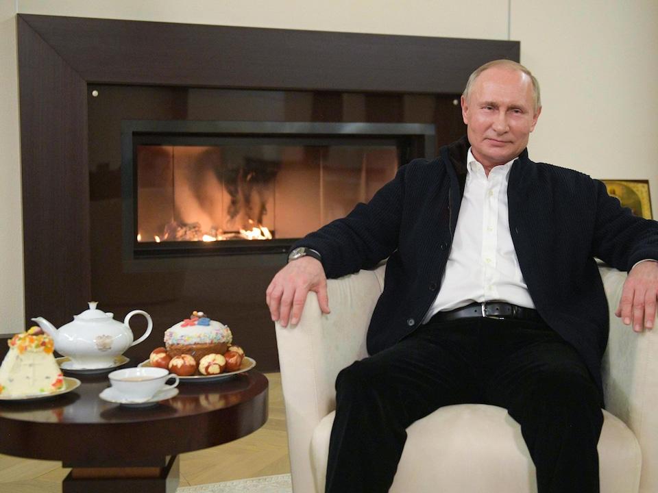 Vladimir Poutine, assis dans un fauteuil devant un foyer à côté d'une table sur laquelle sont déposés des gâteaux de Pâques.