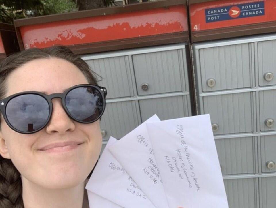 Une jeune femme tient des lettres devant une boîte aux lettres.