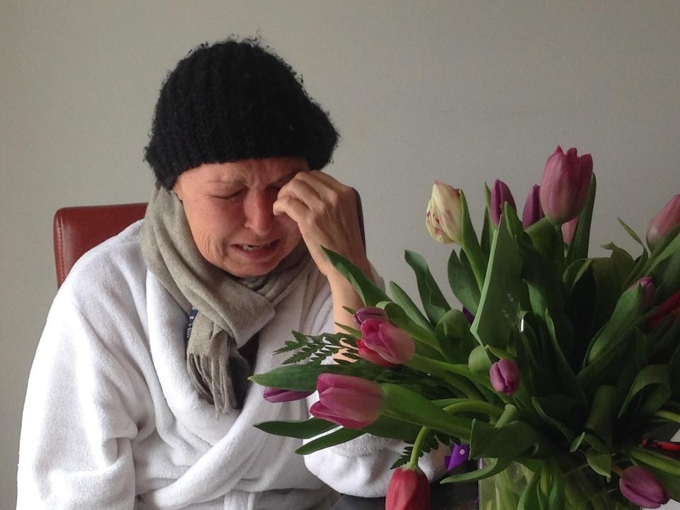Terri pleure devant un bouquet de fleurs