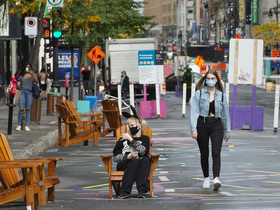 Un homme avec un masque et des oreilles de lapin est assis sur une chaise en plein milieu d'une rue piétonne, dans le Quartier des spectacles, alors qu'une femme, masquée elle aussi, le regarde en marchant.