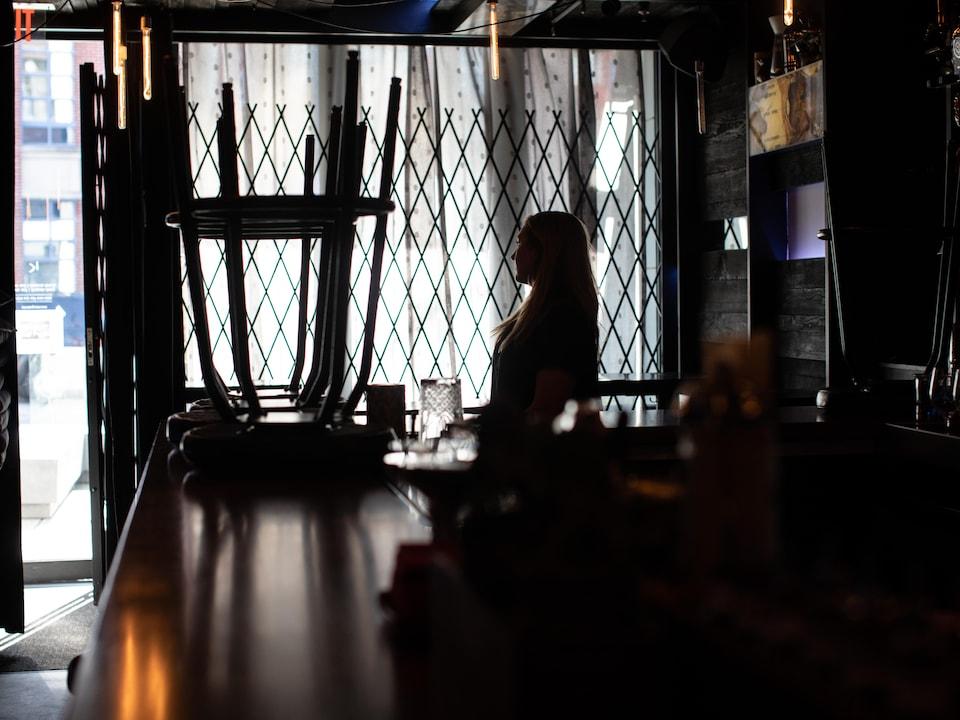 Une femme dans un bar qui est sombre.