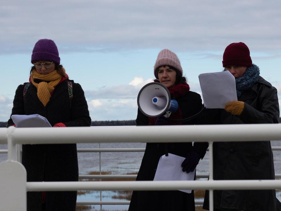 Trois artistes lisent des témoignages sur le bord du fleuve Saint-Laurent, à Rimouski.