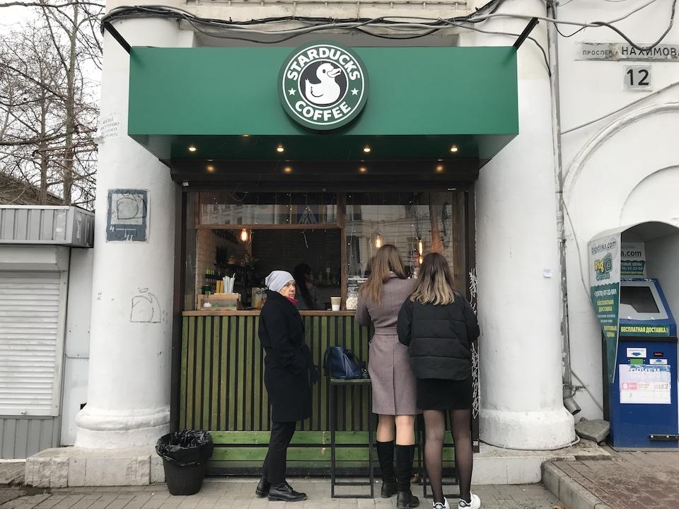 Trois personnes font la file devant un comptoir Starducks qui emprunte les couleurs et le logo de la chaîne américaine Starbucks.