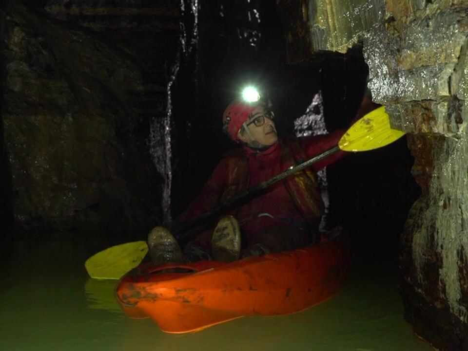 On voit M. Caron dans un kayak, muni d'une lampe, qui explore la caverne de Saint-Léonard.