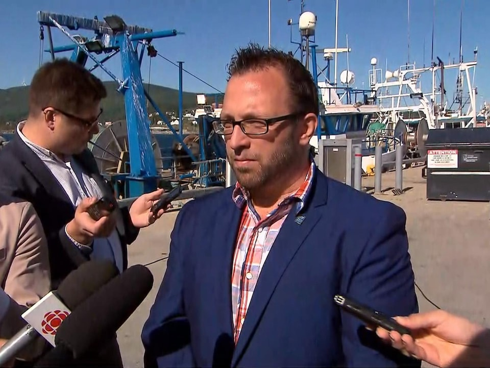 Daniel Côté répond aux questions de journalistes devant un bateau de pêche.