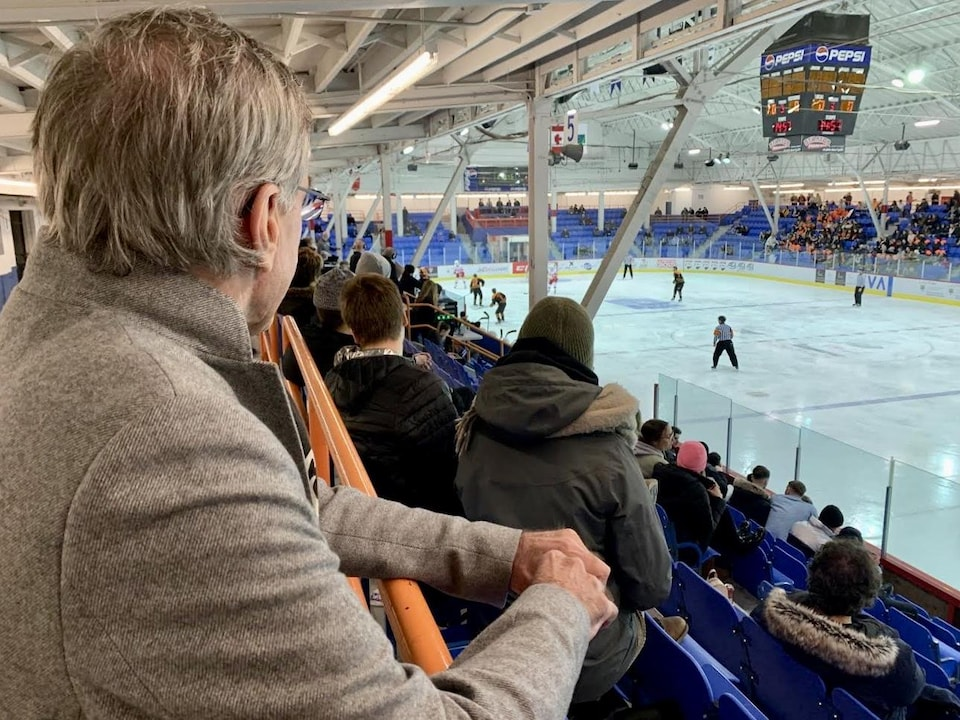 L'homme qui regarde le match de hockey accoudé.