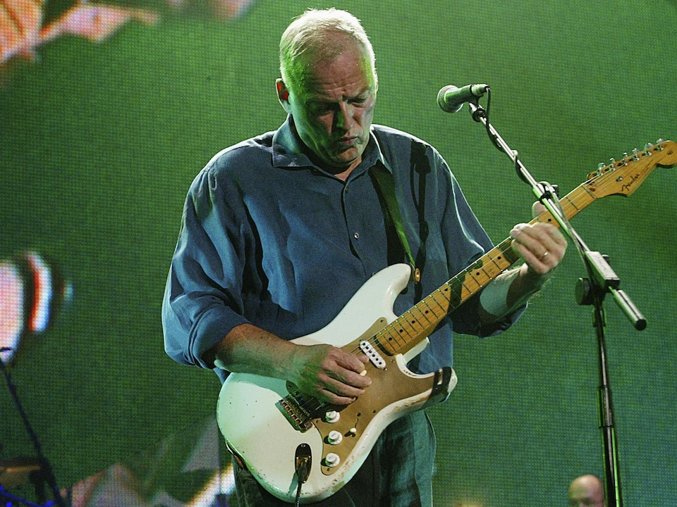 Gilmour, sur scène, s'exécute sur la guitare blanche plutôt usée.