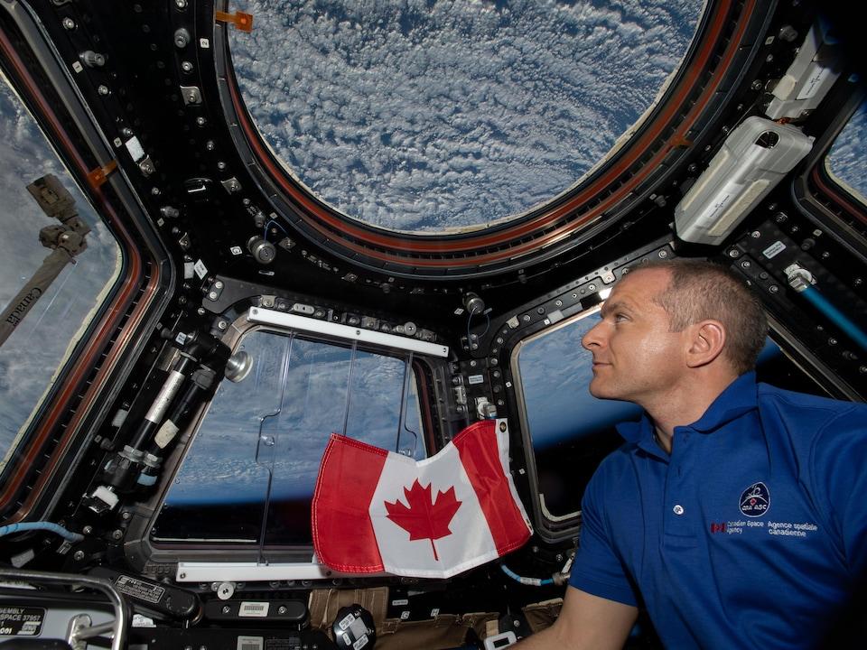 Il regarde la Terre par une fenêtre de la Station spatiale internationale.