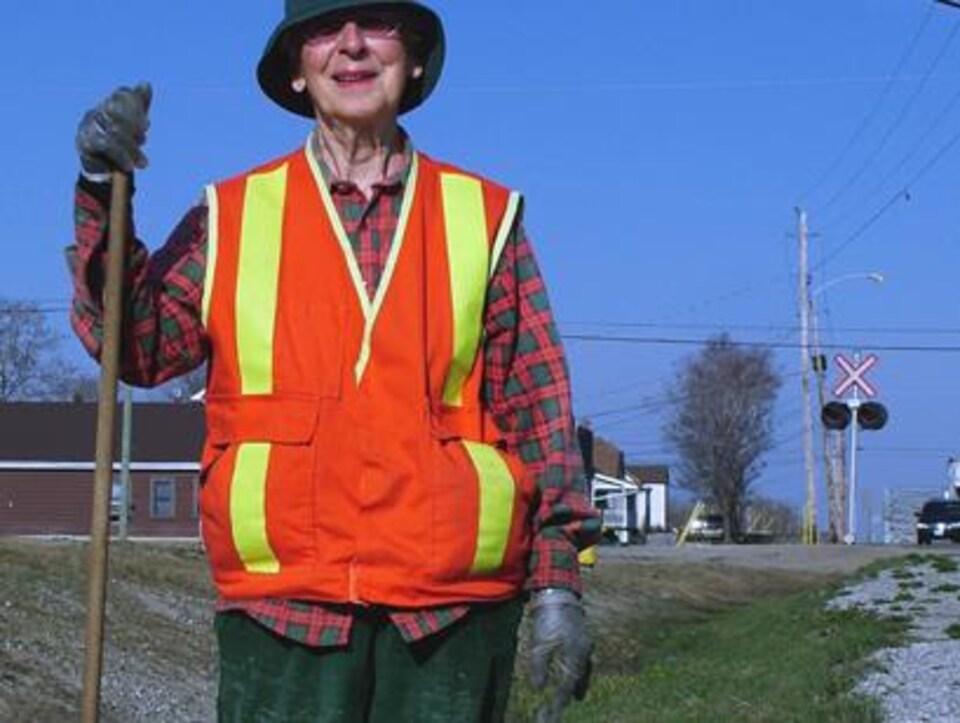 Mme Landry veste fluorescente et rateau à la main