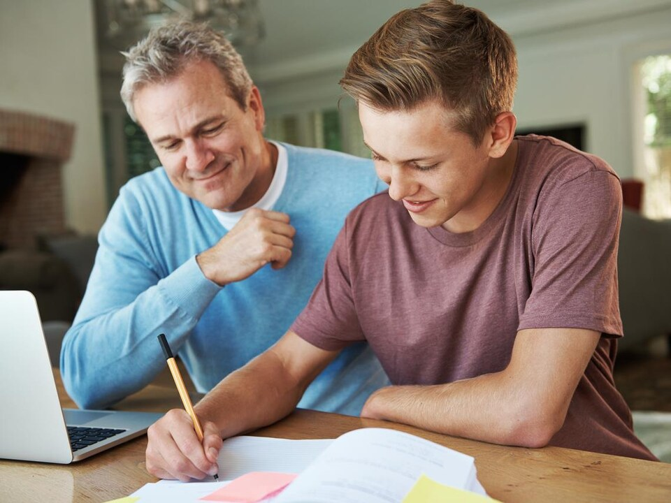 Un adolescent écrit dans un cahier, son père à ses côtés.