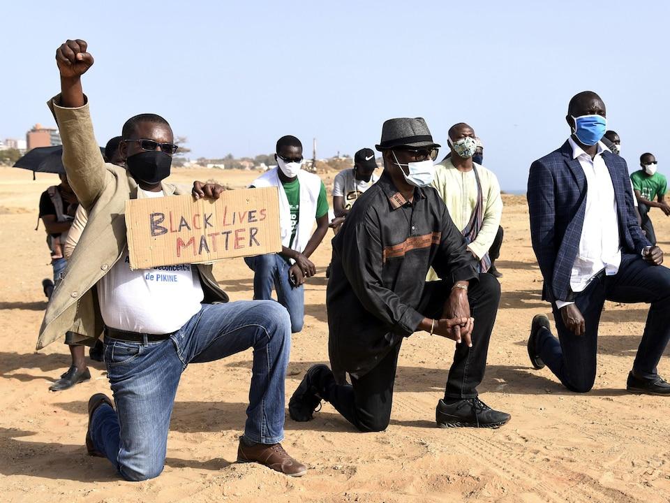 Des manifestants, dont un brandissant le poing et tenant un écriteau de Black Lives Matter, à genoux sur le sable de Dakar, au Sénégal.
