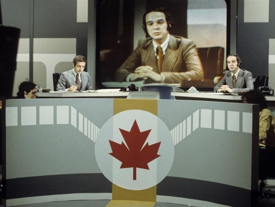 Deux hommes en veston-cravate sont assis autour d'une table ovale. Un a la bouche ouverte, comme s'il parlait, et son image est vue sur une toile derrière lui.