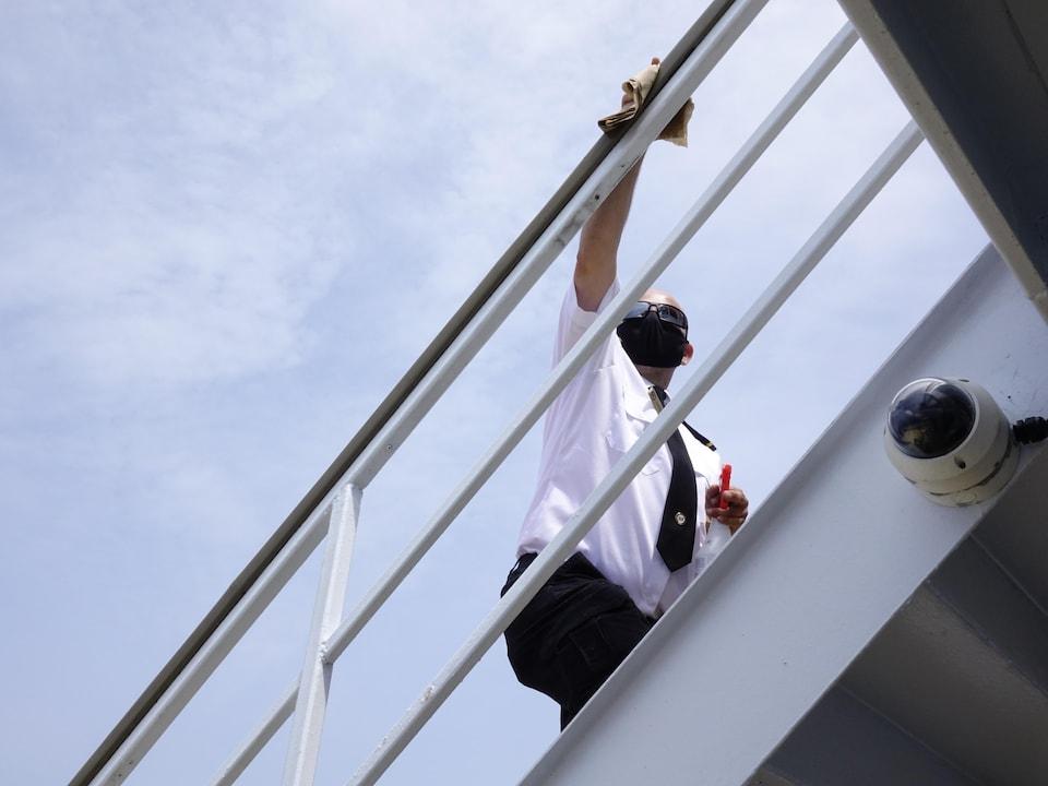 Un matelot désinfecte les rambardes d'escalier.