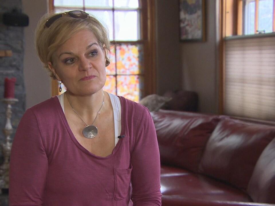 Une femme assise dans son salon écoute attentivement les questions de la journaliste.