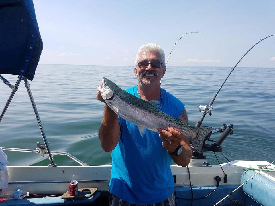 On voit M. Marotte dans son bateau de pêche, souriant à la caméra avec un poisson dans les mains. Derrière lui, la surface du lac Érié par une journée ensoleillée.