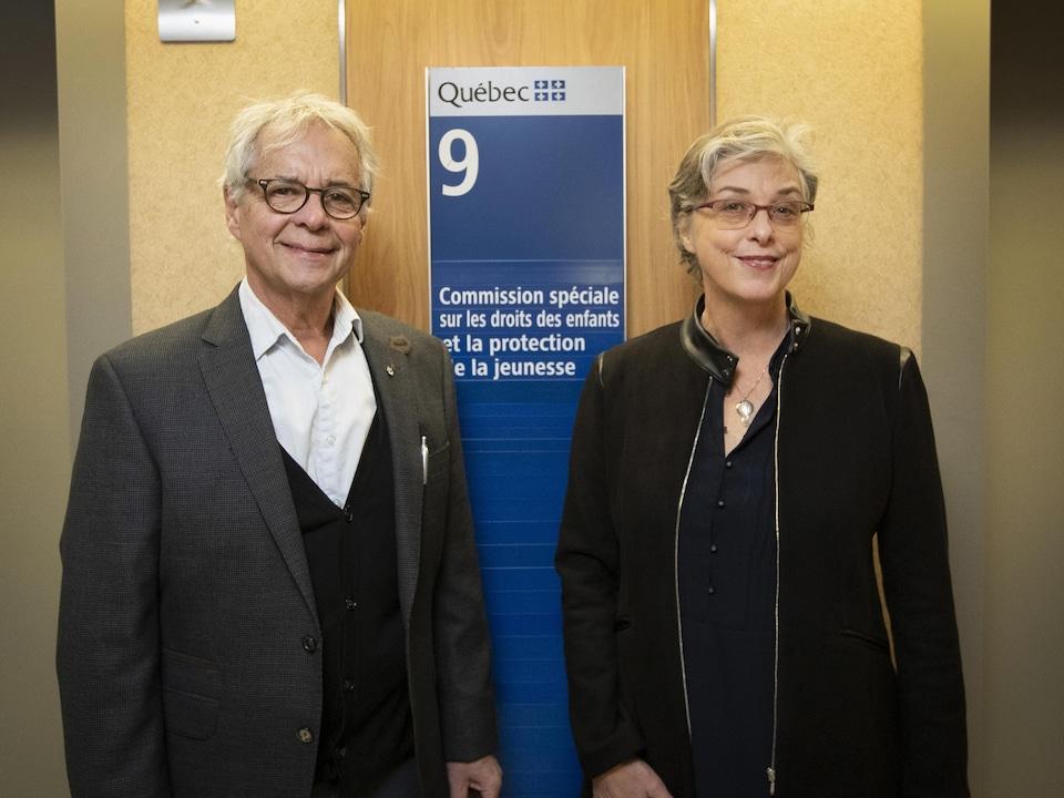 Un homme et une femme souriant devant une affiche qui dit : ''Commission spéciale sur les droits des enfants et la protection de la jeunesse''.