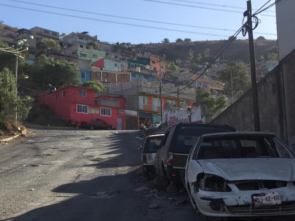 Des carcasses de voiture bordent une rue de la ville.