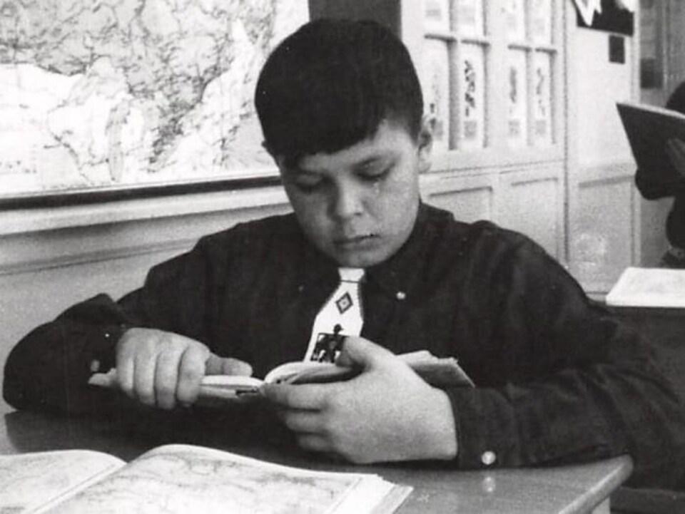 Un garçon lit un livre à son pupitre.