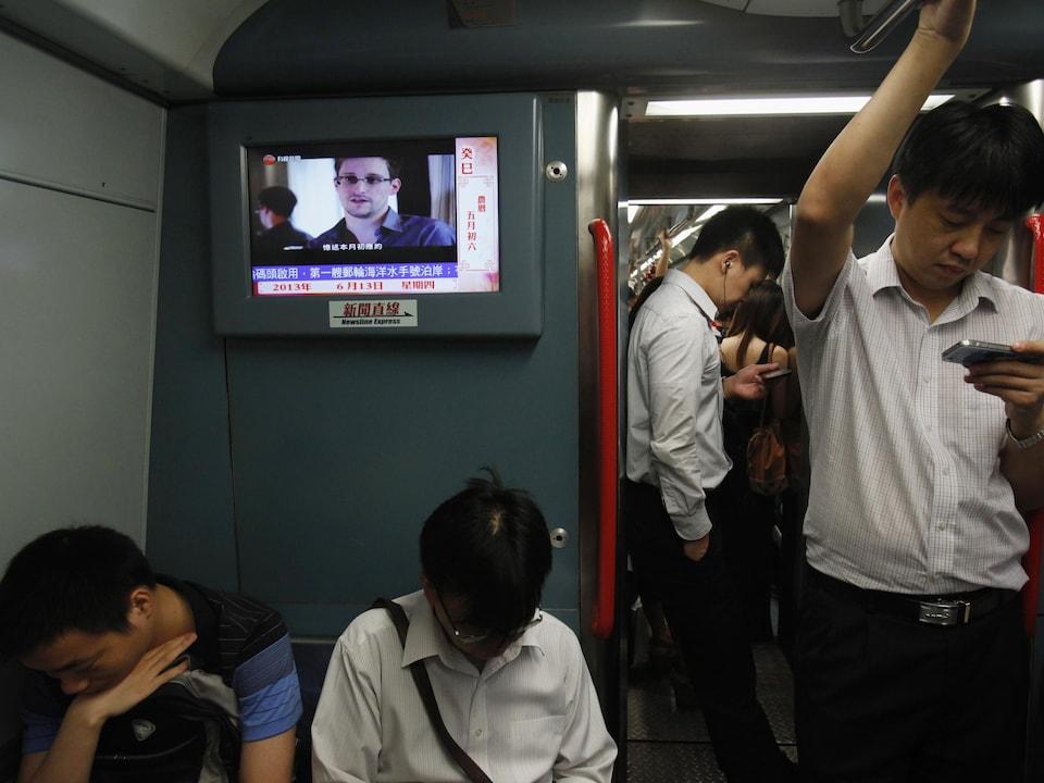 Des passagers debout et assis dans un train avec une télévision au-dessus de leurs têtes.
