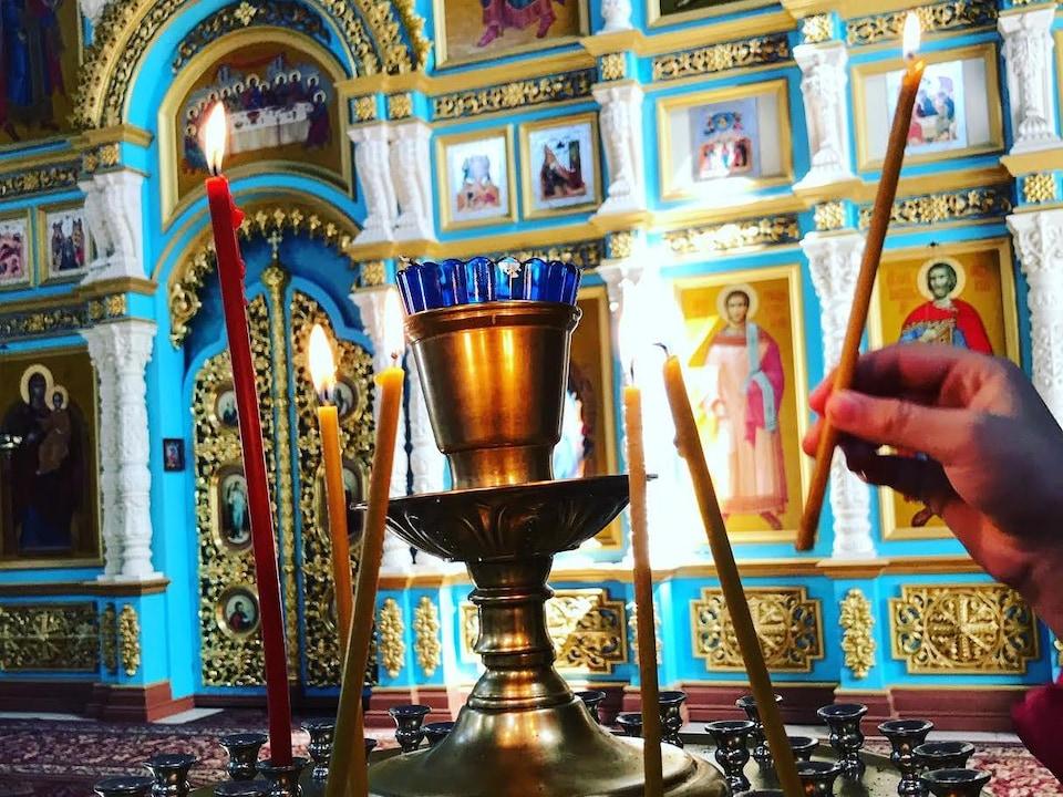 Une main pose une chandelle allumée dans un lieu de culte orthodoxe.