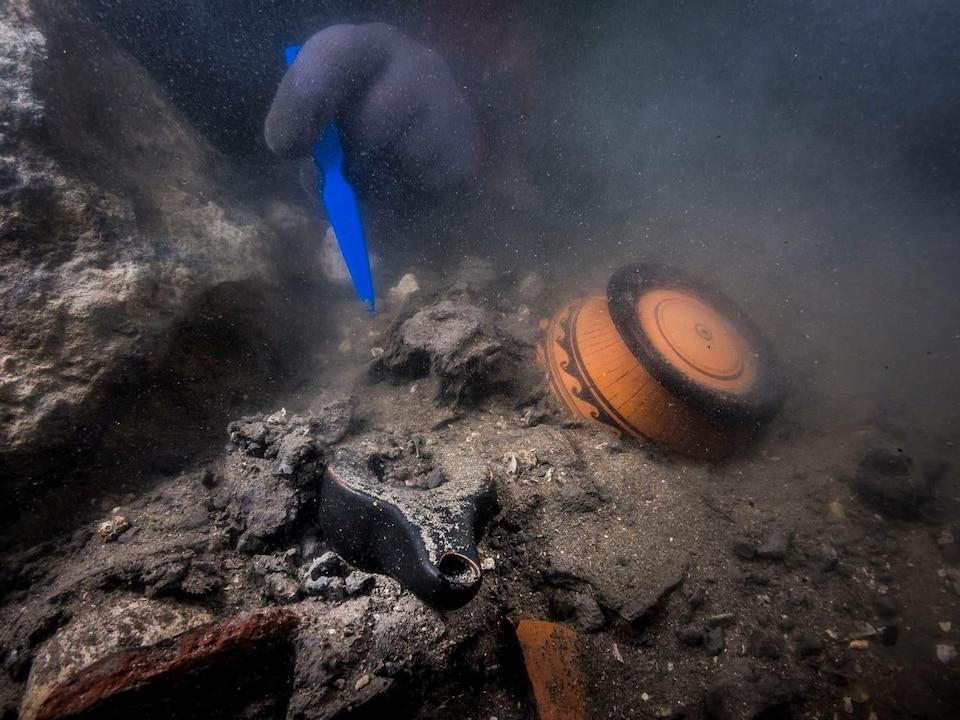 Un plongeur fouille les objets qui se trouvent dans un navire englouti.