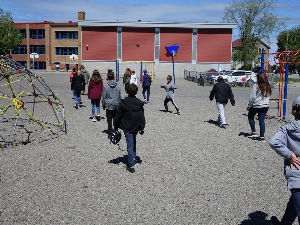 14 élèves tentent de garder une distance de deux mètres entre eux en marchant à la queue leu leu vers l'école.