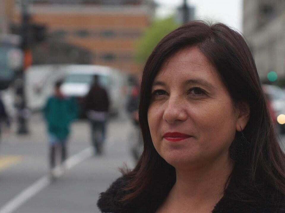 Mme Gaillard dans une rue de Montréal sourit à la caméra.