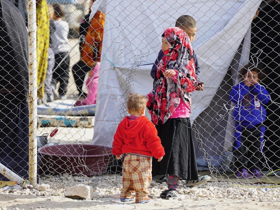 Quatre enfants, dont un très jeune, passent le temps près d'une clôture éventrée.