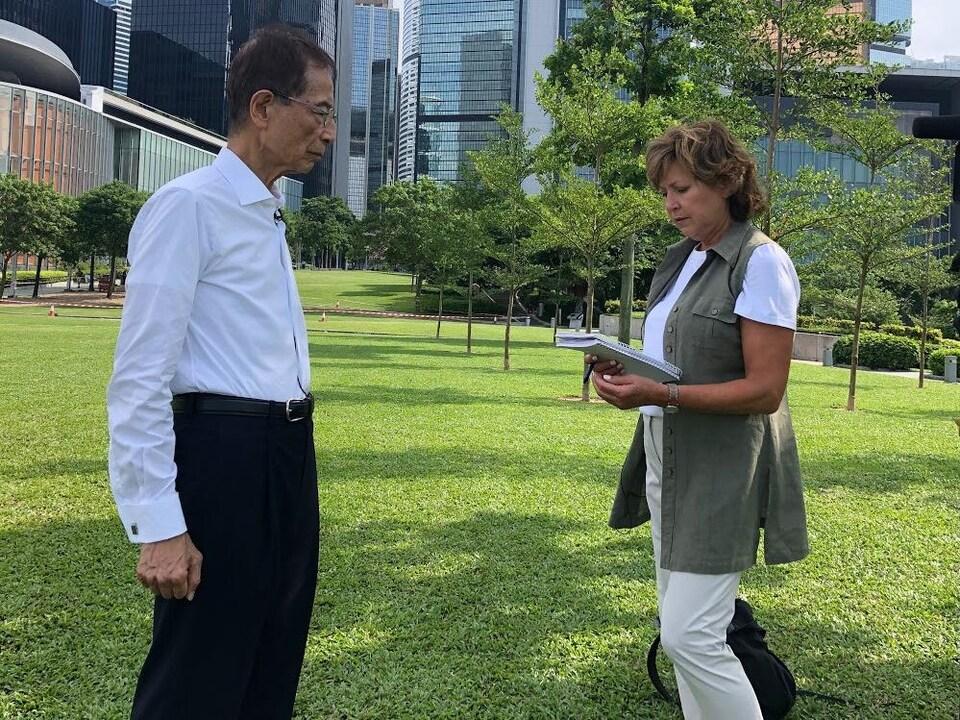 Martin Lee et Céline Galipeau sont debout et se font face sur un parterre devant de grands immeubles.