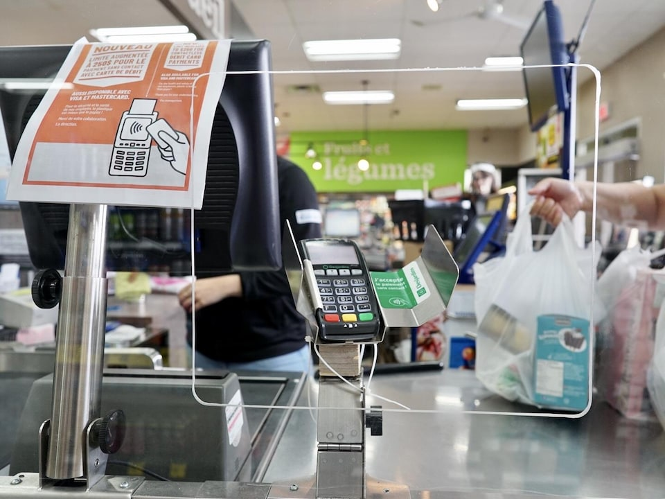 Un plexiglas est installé devant la caisse d'une épicerie.