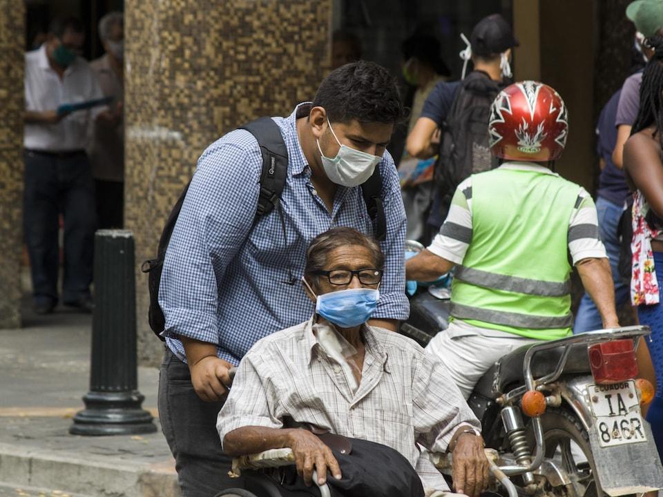 Un homme, le visage couvert d'un masque, pousse un fauteuil roulant en ville.