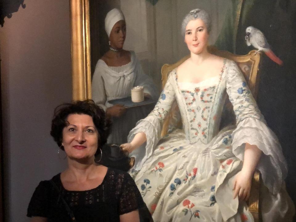 Krystel Gualdé devant une toile illustrant une femme qui se fait servir par une domestique noire.