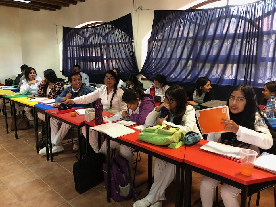 De jeunes gens assis côte à côte dans une salle de classe.
