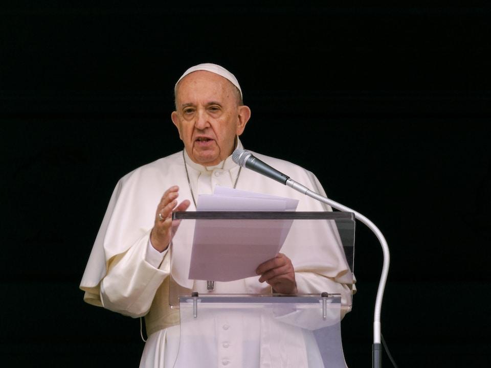 Le pape François se tient derrière un lutrin sur un fond noir.