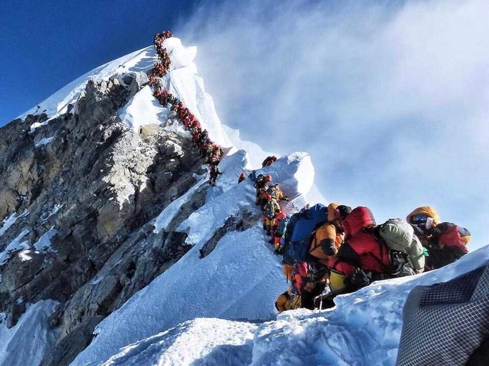 Une longue file d'alpinistes s'étire près du sommet de l'Everest.