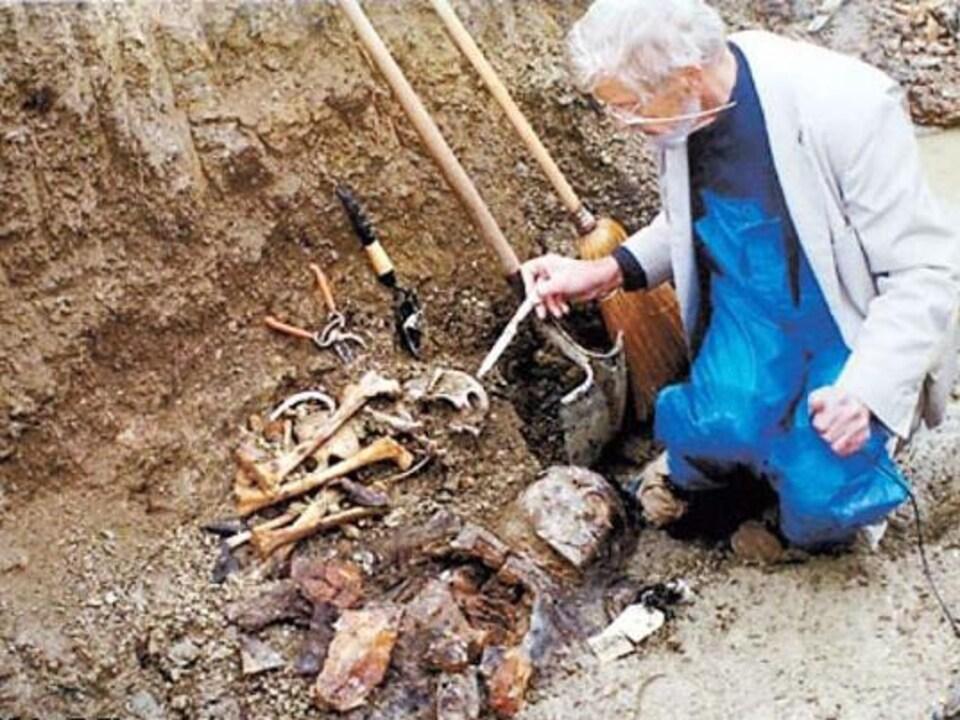 On voit le chercheur qui procède à une fouille dans le sol. Un squelette est à moitié dégagé.