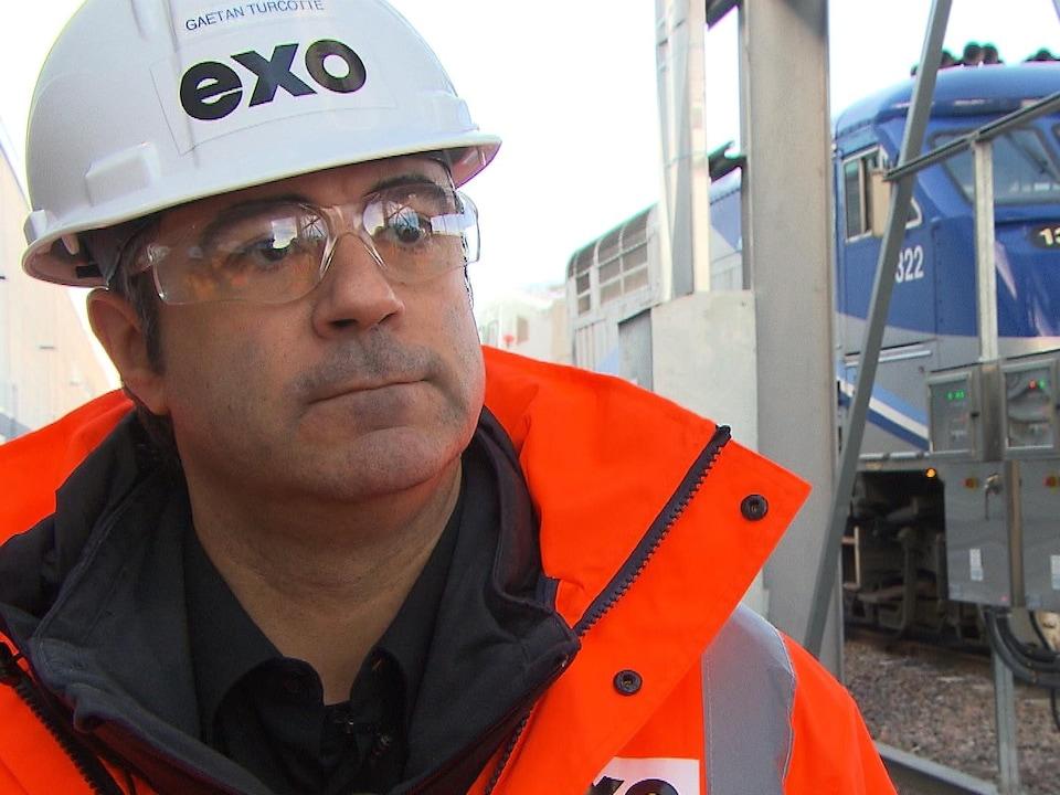 Un homme portant un casque de construction blanc et des lunettes de protection répond aux questions d'un journaliste lors d'une entrevue devant un train arrêté.