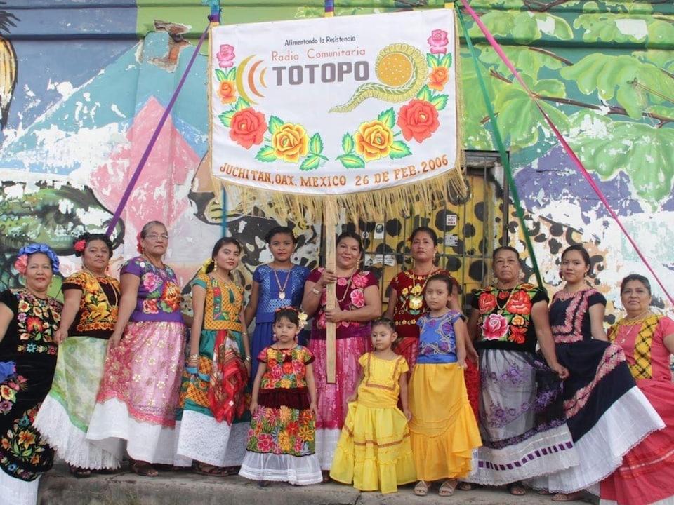 Des femmes et des fillettes aux robes colorées avec une bannière de la radio.