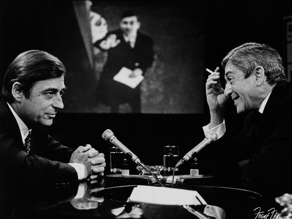 Dans un studio de télévision, François Périer s'entretient avec Fernand Seguin. Une image floue de François Périer, probablement dans un de ses films, est projetée sur le mur du fond.