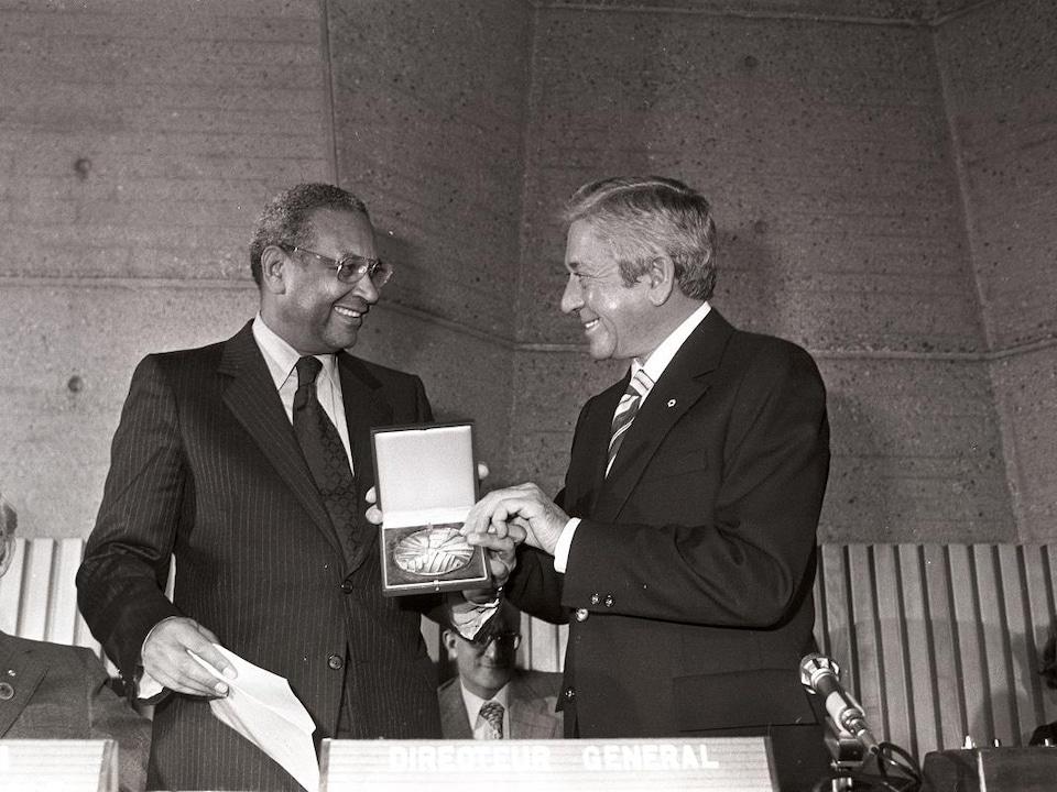 Fernand Seguin, tout sourire, recevant une médaille dans un coffret des mains d'Amadou-Mahtar M'Bow.