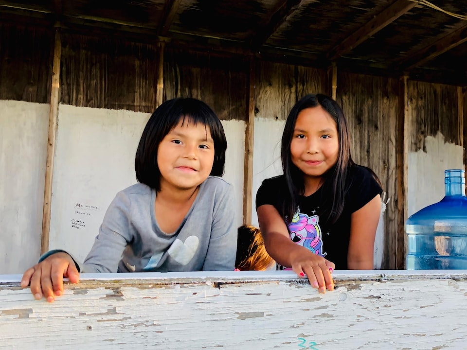 Deux jeunes filles appuyées sur un cadre de fenêtre.