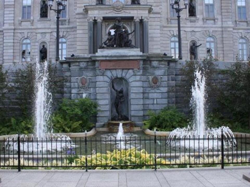 Fontaine avec fleurs devant deux statuts représentant une famille Abénaquis devant l'Assemblée nationale.