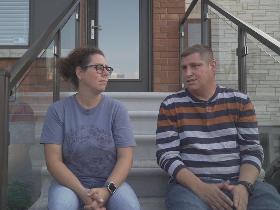 Le couple est assis devant sa maison, dans les escaliers.