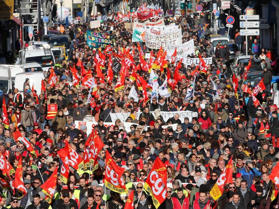 Des milliers de personnes marchent dans la rue.